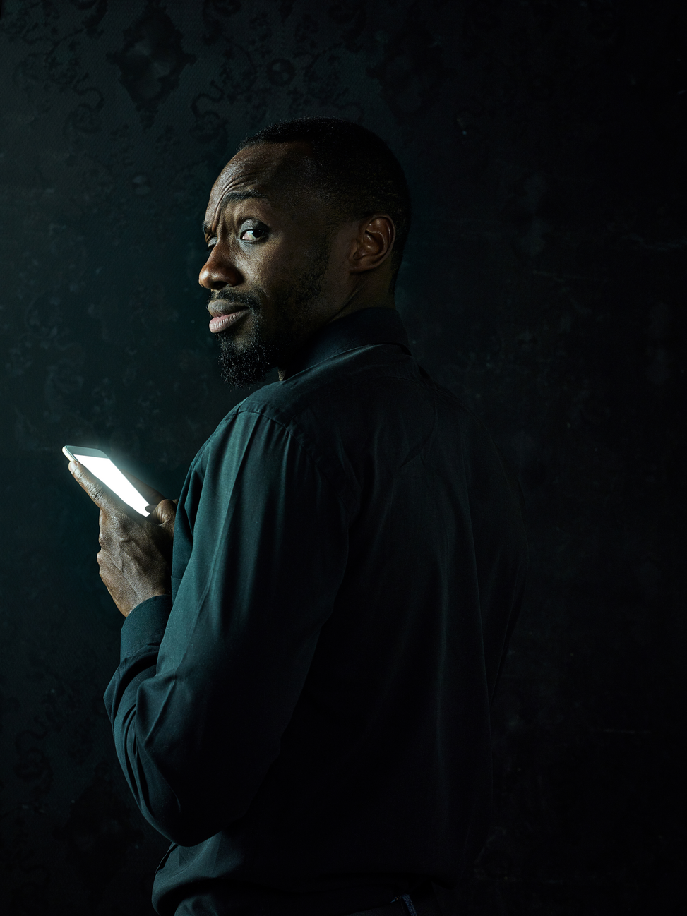 rsz_young-serious-black-african-man-thinking-while-talking-mobile-phone-against-black-studio-background